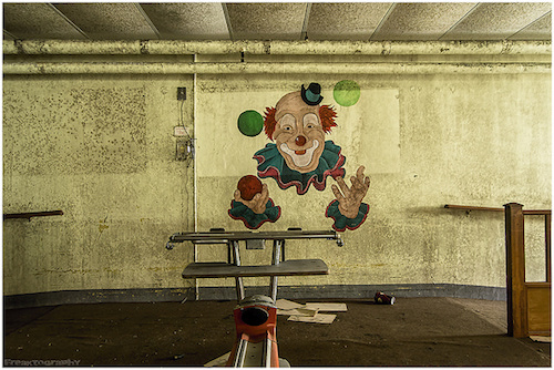 Creepy clown painting on the wall of an abandoned psychiatric facility